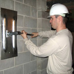 installing a wall anchor to repair an bowing foundation wall in Milton