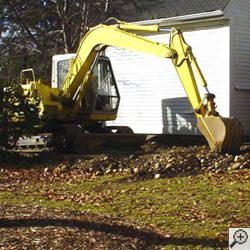 A backhoe excavating a foundation to install an exterior perimeter weeping tile drainage system in Calhoun.